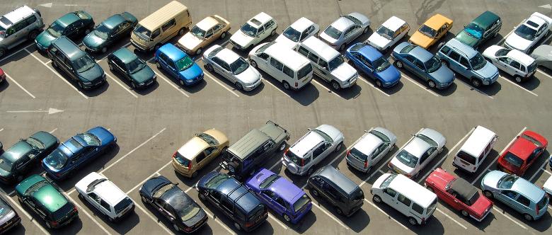 Auf einem vollen Parkplatz passiert es oft, dass eine Autotür gegen ein anderes Auto kracht.